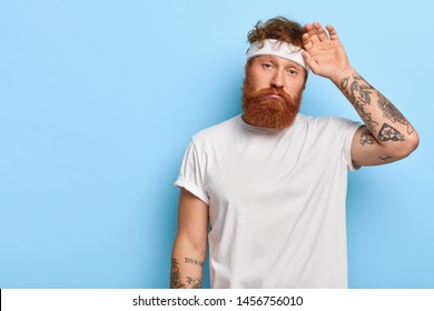 Fatigue sportsman wipes sweat on forehead, has unhappy look, wears white headband, has tattooed arms, had active training, leads healhthy lifestyle, stands over blue wall, blank free space on left