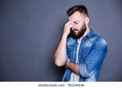 Fatigue at work. A young bearded man holds his hands over his head against a gray background.