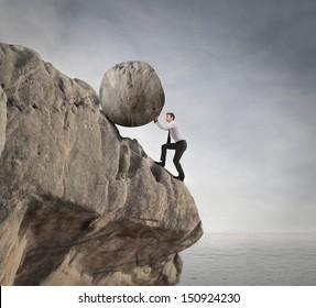 fatigued businessman supports large boulder