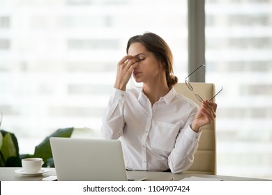 Fatigued businesswoman taking off glasses tired of computer work, exhausted employee suffering from blurry vision symptoms after long laptop use, overworked woman feels eye strain tension problem