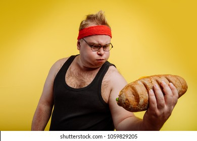 Fatigued funny fat man sweats while lifting burger
