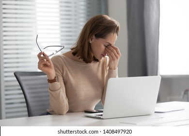 Fatigued stressed young businesswoman secretary take off glasses at workplace tired of computer syndrome overwork feel eye strain headache suffer from bad blurry vision sight problem at work concept