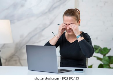 Fatigued tired young woman is holding glasses, rubbing her eyes, suffering from eyestrain in front of a pc screen at home. Pain in eyes, vision problems after long time working on laptop computer