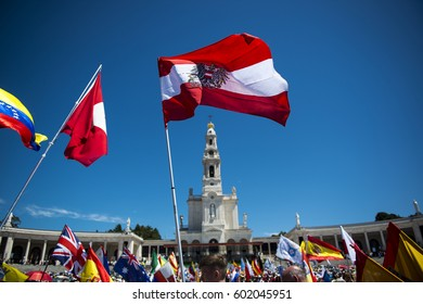 Fatima, Portugal - May 13, 2014: People waving flags from different countries at the Sanctuary of Fatima during the celebrations of the apparition of the Virgin Mary in Fatima, Portugal.
