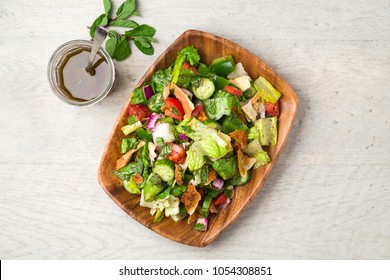 Fattoush salad top flat lay view. The key ingredient in this middle eastern dish is the toasted pita bread which is mixed with healthy vegetables, herbs and a dressing made with lemon and sumac.
