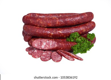 Fatty smoked sausage whole and partially sliced. Meat product decorated with branch of parsley. Isolated on white background