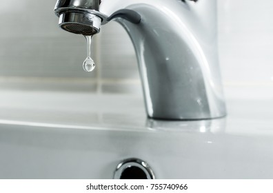 Faucet with a drop of water. Water leaking and saving.