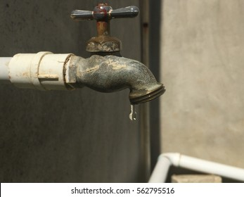 A faucet dropping the las tear of water.