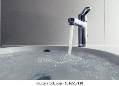 faucet with flowing water in wash sink