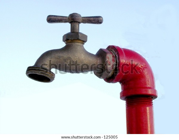 faucet on a red pipe against the sky
