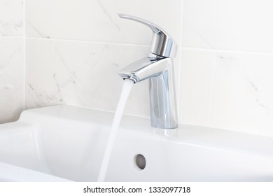 Faucet pouring water into sink. Close up.