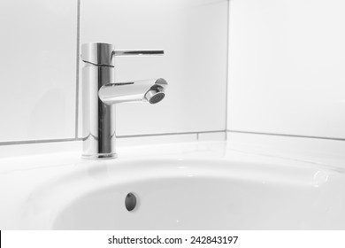 Faucet and white basin in a hotel bathroom