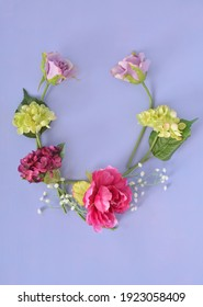 Faux Blumen auf violettem Hintergrund in vertikalem Format mit Platz für Text.