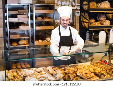 Favorable male pastry maker demonstrating croissant in bakery.