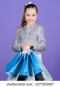 Favorite brands and hottest trends. Girl with shopping bags violet background. Shopping and purchase. Black friday. Sale discount. Shopping day. Child hold bunch packages. Kids fashion. Birthday girl.
