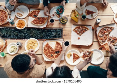 Favorite food. Close up top view of young people eating pizza while having a dinner party indoors