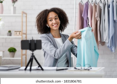 Favorite job and fashion industry. Focus on happy african american lady recording online style lesson and showing blue shirt on smartphone webcam in studio at home, during covid-19 pandemic