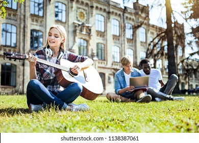 Favorite leisure activity. Attractive blonde lady in casual sitting on grass and smiling while playing guitar and relaxing outdoors.