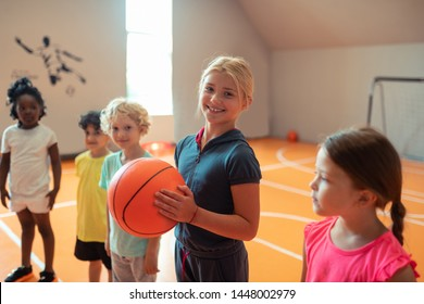 Favorite lesson. Smiling girl holding a basketball standing next to her classmates during sports class.