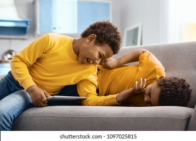 Favorite pastime. Upbeat little brothers lying on the sofa and tickling each other, having fun while one of the boys holding a tablet