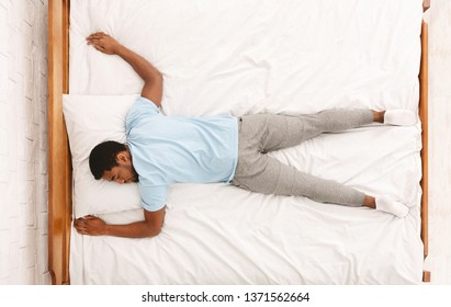 Favorite pose for sleep. African american millennial guy sleeping, lying on stomach in bed, top view