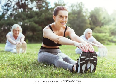 Favourite activity. Cheerful healthy young woman smiling and holding her feet while enjoying sport exercises
