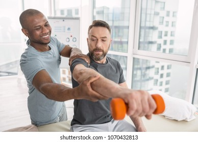 Favourite job. Delighted nice therapist smiling to his patient while helping his to lift a hand