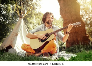 Favourite music. Delighted happy man sitting on the ground while playing a music instrument