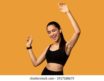 Favourite Song. Portrait Of Excited Young Sportive Lady Wearing Wireless Earbuds Listening To Music And Dancing Isolated Over Orange Studio Background. Lady With Closed Eyes Enjoying Playlist