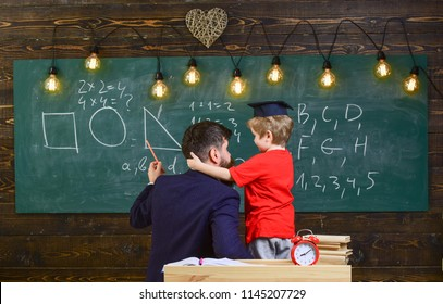 Favourite teacher concept. Teacher with beard, father teaches little son in classroom, chalkboard on background. Boy, child in graduate cap listening teacher, chalkboard on background, rear view.