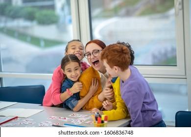 A favourite teacher. A group of schoolchildren hugging a smiling teacher