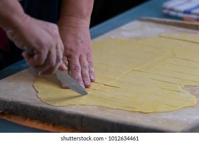 Faworki - woman's hands cutting raw dough. Preparing dough for faworki.