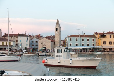 Fazana, Croatia - July 28, 2018: View of the harbour of Fazana with the market and the church in the background in the evening sun, Croatia.