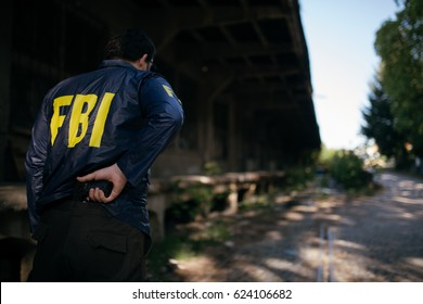 FBI agent in action with a pistol, rear view