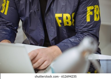 FBI agent in his office using laptop, part of