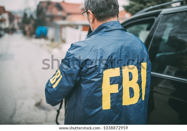 The FBI agent stands beside his car
