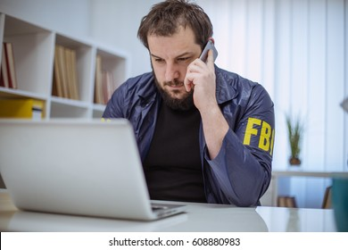 FBI agent working in his office on laptop and talking on mobile phone