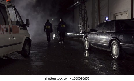 FBI agents work at the scene at night, police car with lights and ambulance background. Back view on three FBI agents go towards criminal scene