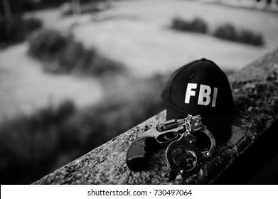 FBI cap with revolver and handcuff.