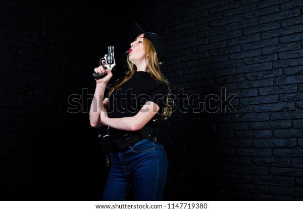 FBI female agent in cap and with gun at studio against dark brick wall.