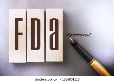 FDA approved words made with wooden blocks. Food and drugs association concept.