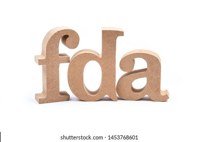 FDA wood alphabet isolated on white background, abbreviation of Food and Drug Administration