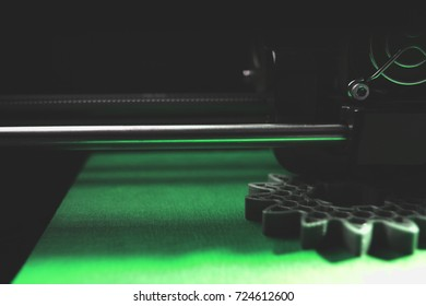 FDM 3D-printer manufacturing spur gears from silver-gray filament on blue print tape - dimmed part view on print head, print bed and object - green shade - background blanked out blurry