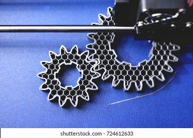 FDM 3D-printer manufacturing spur gears from silver-gray filament on blue print tape - top view on object, print bed and print head - matte look - foreground blanked out blurry