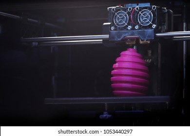 FDM 3D-printer manufacturing wound pink easter egg sculpture - front view on object and print head - technical look with selective, neutral light - background blanked out blurry