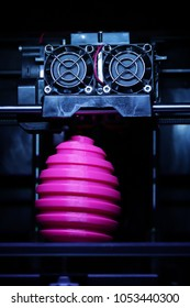 FDM 3D-printer manufacturing wound pink easter egg sculpture - front view on object and print head - portrait composition in cold futuristic light mood - background blanked out blurry