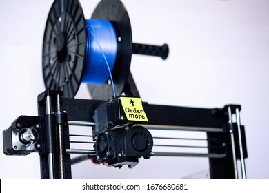 A FDM style 3d printer that has a spool of filament that is running low, and a sticky note as a reminder to order more silk PLA type of filament.