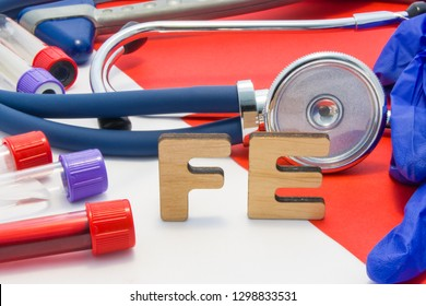 FE medical abbreviation meaning total iron or ferrum in blood in laboratory diagnostics on red background. Chemical name of FE is surrounded by medical laboratory test tubes with blood, stethoscope