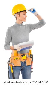 feamle wearing working clothes with construction tools holding blue clipboard and yellou helmet looking at a distance isolated on white background
