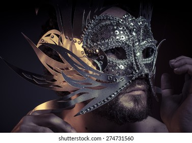 Fear, bearded man with silver mask Venetian style. Mystery and renaissance